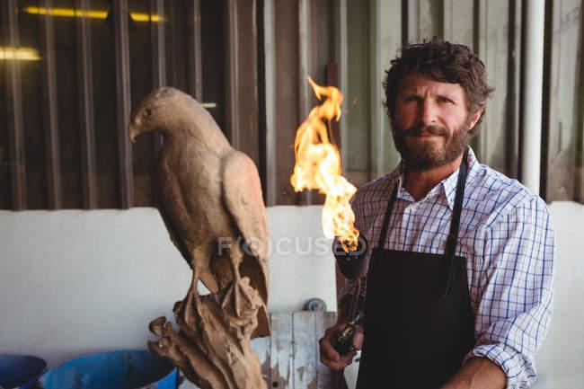 Portrait of confident craftsman holding burner in workshop — Stock Photo