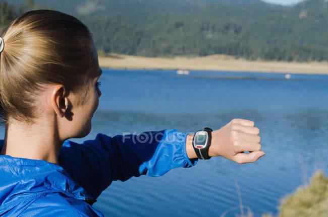 Seitenansicht einer Frau, die auf eine Armbanduhr blickt, während sie am See steht — Stockfoto