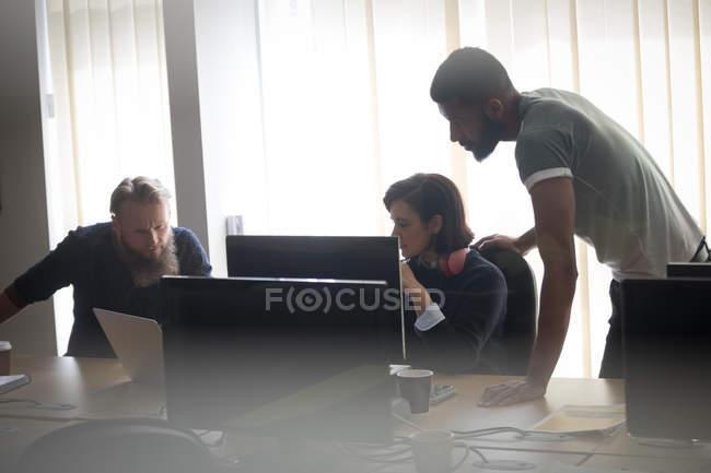 Коллеги, работающие вместе за столом в офисе — стоковое фото