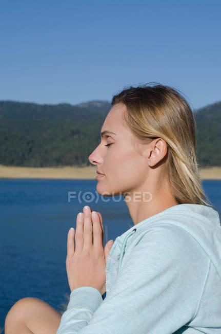 На березі озера біля самки - туристки моляться. — стокове фото