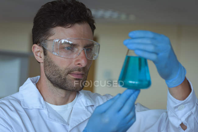 Attentive university student doing a chemical experiment in laboratory — Stock Photo