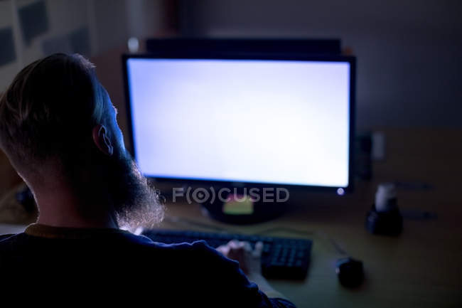 Rear view of executive working on personal computer at desk — Stock Photo