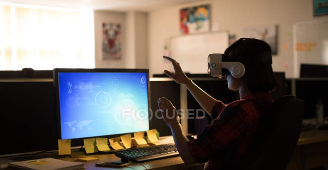 Executive using virtual reality headset while working at desk in office — Stock Photo