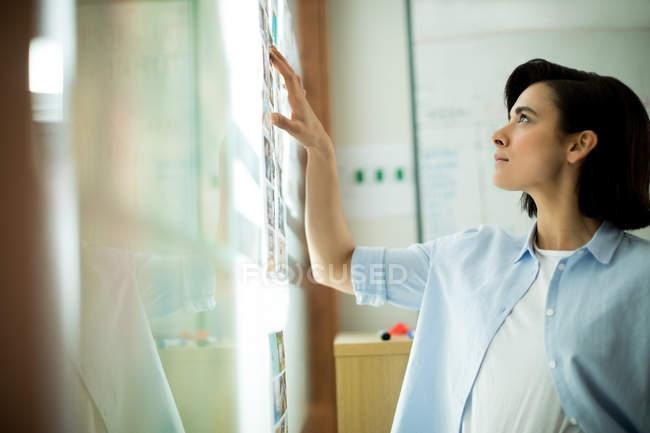 Ejecutivo mirando fotos palo en vidrio en la oficina - foto de stock