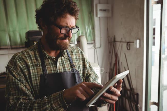 Attentive craftsman using digital tablet in workshop — Stock Photo