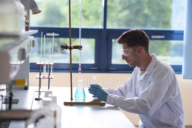 Side view of male college student practicing chemistry experiment in lab — Stock Photo