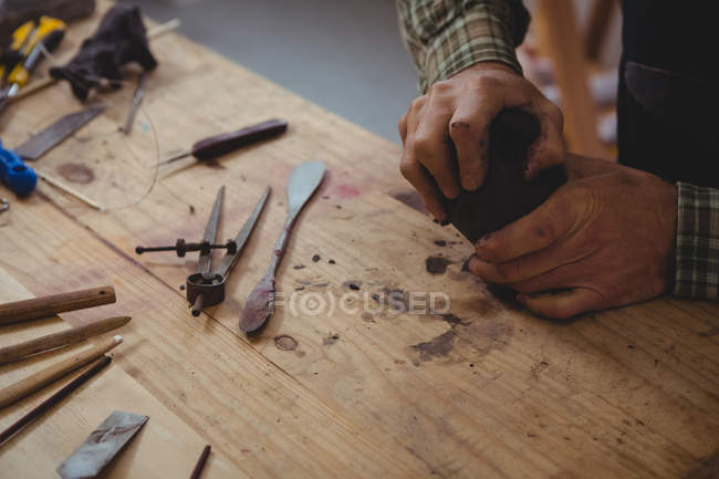 Craftsman working on clay sculpture in workshop — Stock Photo