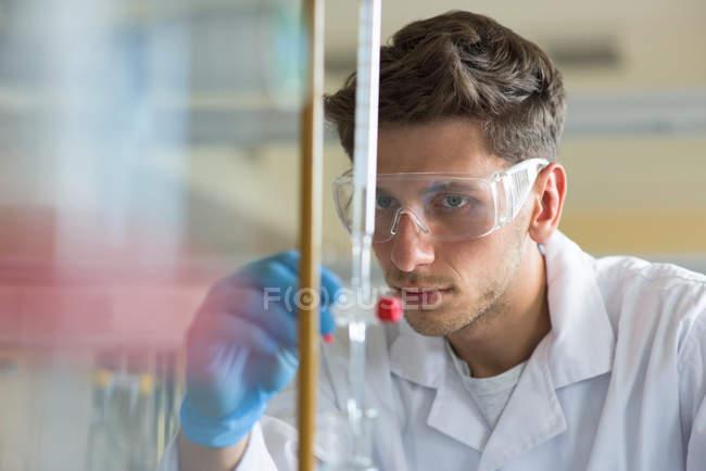 Gros plan d'un étudiant pratiquant une expérience en laboratoire — Photo de stock