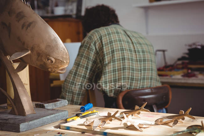 Verschiedene Skulpturen auf Holztisch in Werkstatt — Stockfoto
