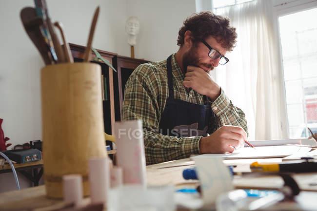 Художник малює скульптуру в майстерні. — стокове фото