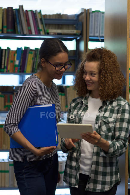 Adolescente souriante montrant l'ordinateur tablette à un ami tout en se tenant dans la bibliothèque — Photo de stock