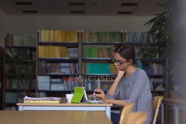 Étudiante qui utilise une tablette numérique alors qu'elle est assise au bureau en classe — Photo de stock