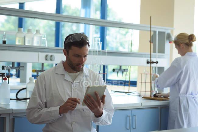 Estudiantes universitarios discutiendo informes en laboratorio - foto de stock
