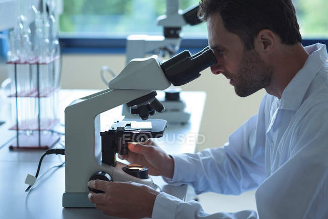 University student doing experiment on microscope in laboratory at college — Stock Photo