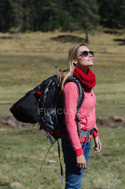 Side view of female hiker with sunglasses standing on field — Stock Photo