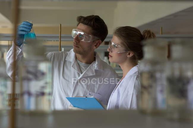 Giovani studenti universitari che praticano l'esperimento di chimica in laboratorio — Foto stock
