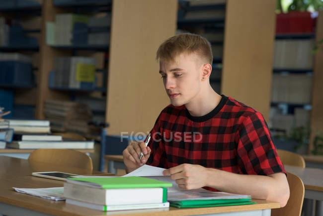 Estudiantes jóvenes universitarios que estudian en la mesa de trabajo en el aula - foto de stock