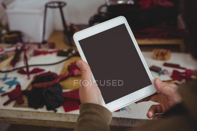 Mid-section of craftsman using digital tablet in workshop — Stock Photo
