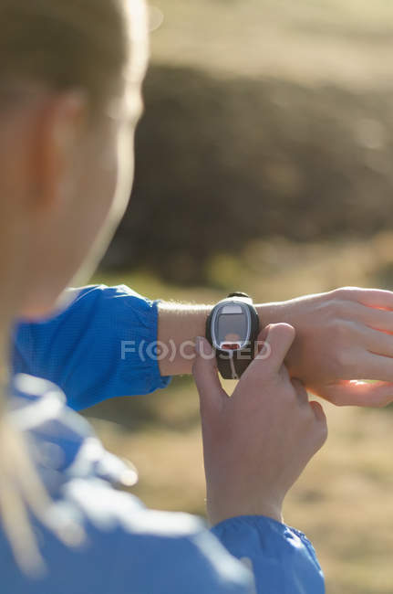 Женщина настраивает наручные часы, стоя на поле — стоковое фото