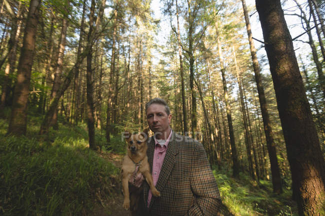 Mature man with his pet dog in forest — Stock Photo