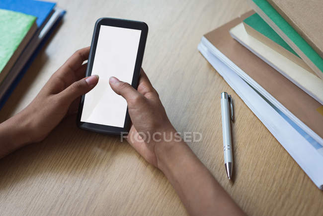 Cropped image of teenage girl using smartphone at desk in classroom — Stock Photo
