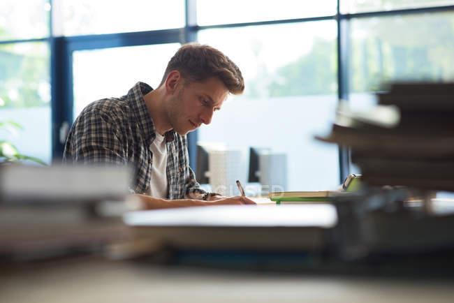 Vue latérale du jeune étudiant mâle étudiant au bureau par fenêtre dans la salle de classe — Photo de stock