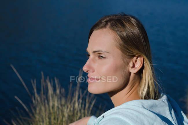 Высокий угол обзора вдумчивый женский турист на берегу озера в солнечный день — стоковое фото