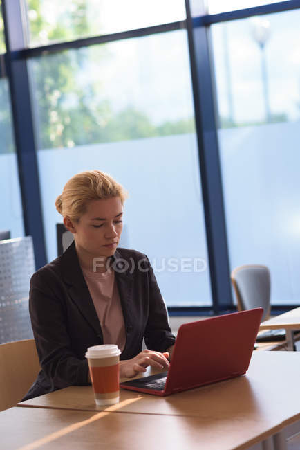 Attentive university student using laptop in college — Stock Photo