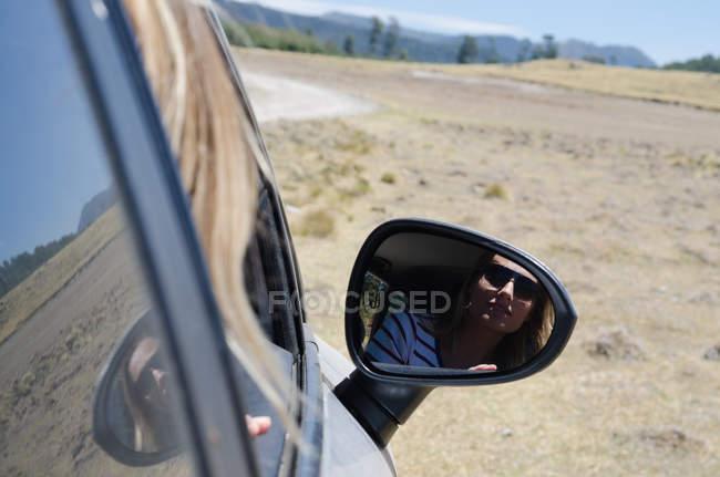 Крупный план женщины, отражающейся в боковом зеркале автомобиля в солнечный день — стоковое фото