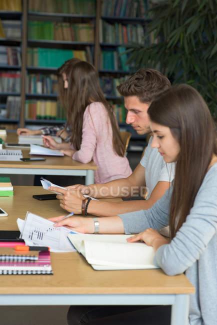 Vue latérale des étudiants qui étudient au bureau en salle de classe — Photo de stock