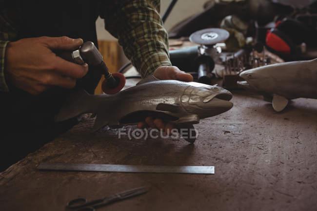 Середній прошарок ремісника, який формує металеву рибу в майстерні — стокове фото