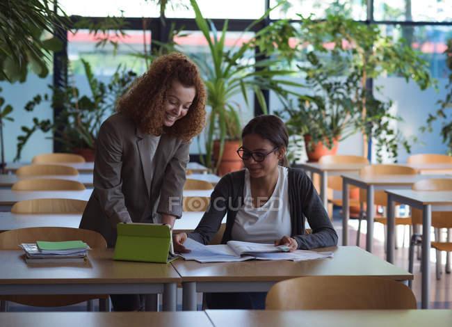 Estudantes do sexo feminino sorrindo estudando na mesa em sala de aula — Fotografia de Stock