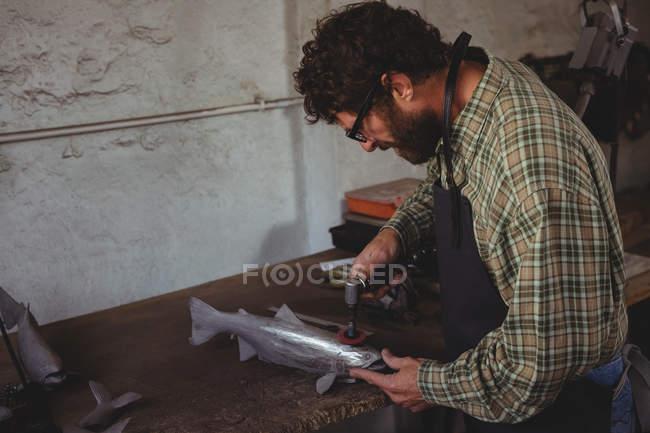 Ремісник - майстер з виготовлення металевої риби у майстерні. — стокове фото