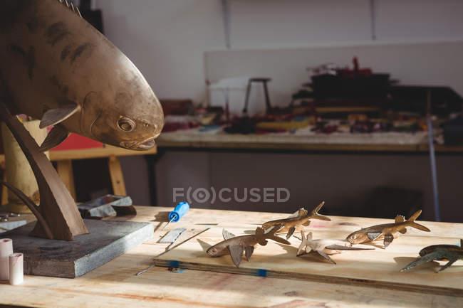 Різні скульптури на дерев'яному столі в майстерні. — стокове фото