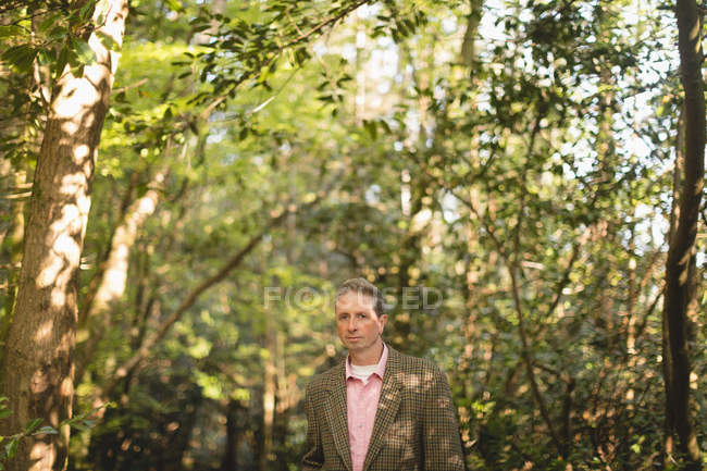Portrait of mature man standing in forest — Stock Photo