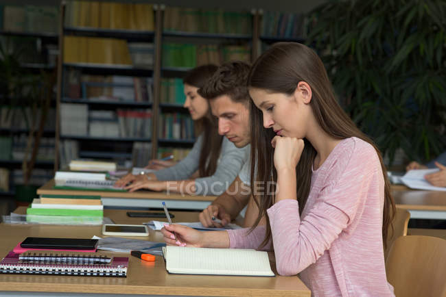 Estudiantes universitarios que estudian en la mesa en el aula - foto de stock