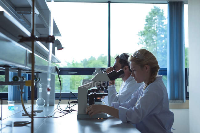 University students doing experiment on microscope in laboratory at college — Stock Photo
