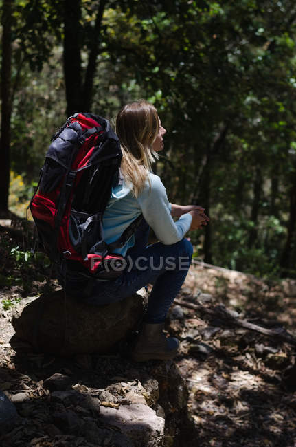 High angle view of female hiker with backpack sitting on rock at forest — Stock Photo