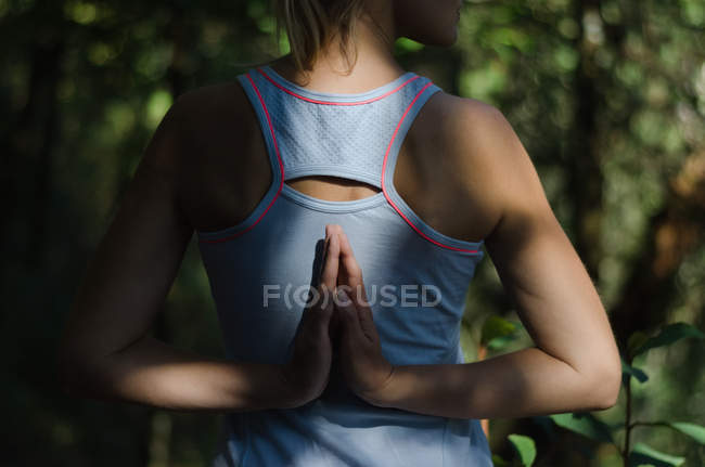 Rear view of female hiker exercising on field — Stock Photo