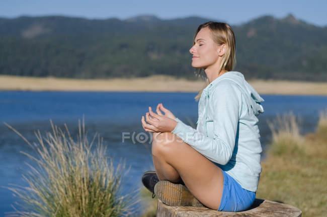 Вид сбоку на женщину-туристку, сидящую на дереве на берегу озера — стоковое фото