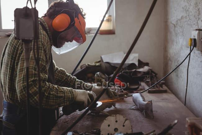У майстерні майстер шиє метал за допомогою електричного інструмента. — стокове фото