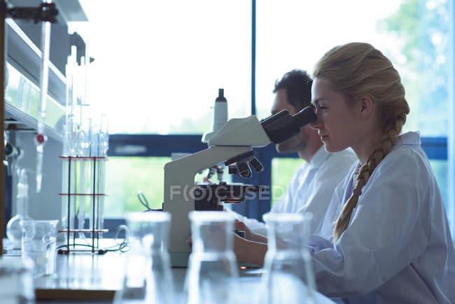 Estudantes universitários fazendo experiência em microscópio em laboratório na faculdade — Fotografia de Stock