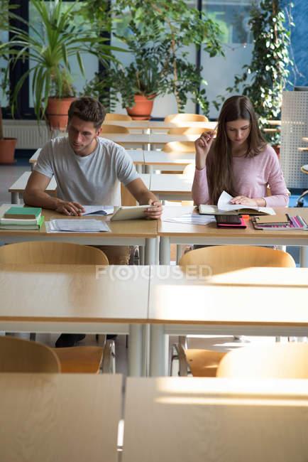 Estudiantes universitarios jóvenes que estudian en la mesa en un ambiente tranquilo - foto de stock