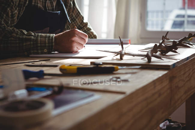 Mid-section of craftsman drawing sculpture design in workshop — Stock Photo