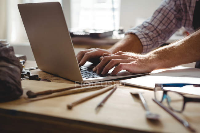 Sezione media dell'artigiano che usa il computer portatile alla scrivania — Foto stock