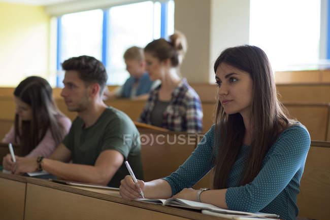 Studenti universitari che si concentrano durante la lezione in aula — Foto stock