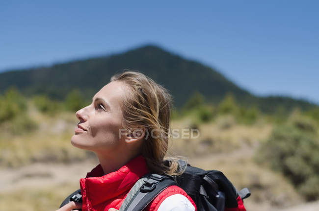 Female hiker looking up while standing against sky — Stock Photo