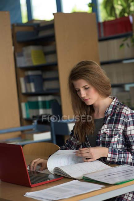 Estudiantes jóvenes que utilizan portátil mientras estudian en el escritorio en el salón de clases. - foto de stock