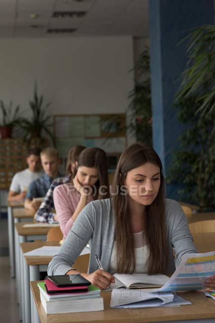 Студенти, які сидять за столом під час екзамену в класі. — стокове фото
