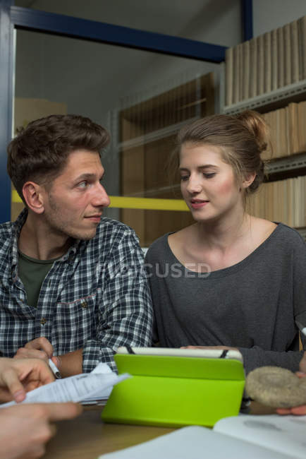 Étudiants du collège discutent tout en étudiant au bureau en classe — Photo de stock